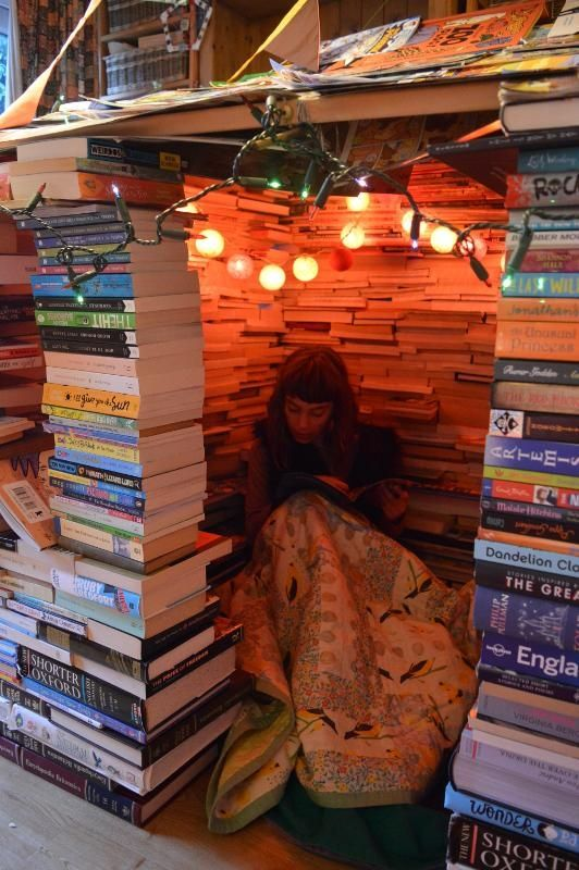 Girl hides in stack of books reading.